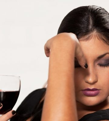 Girl with red wine is taking hard decision